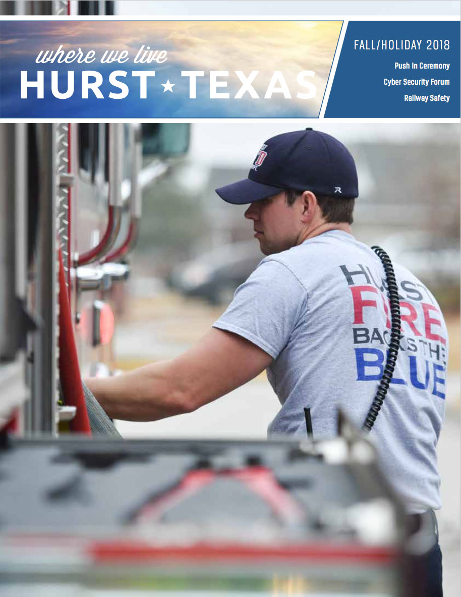 City of Hurst Fall/Holiday Where We Live magazine cover for Fall/Holiday 2018. Firefighter by fire engine.